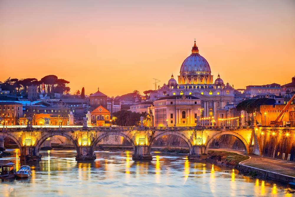 sun setting over Rome, Italy creating purple lighting on the buildings and river