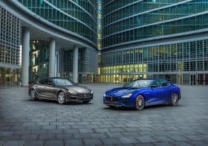 Two Maserati Ghiblis parked in front of high-end business buildings
