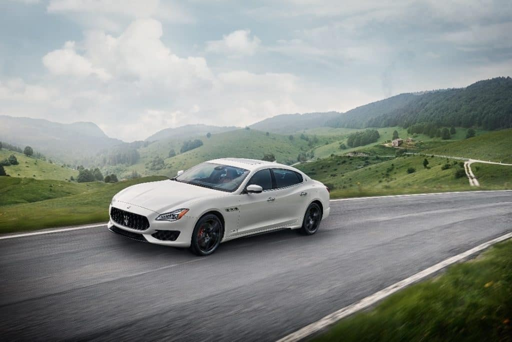 White 2019 Maserati Quattroporte GTS driving through the countryside with hills in the background