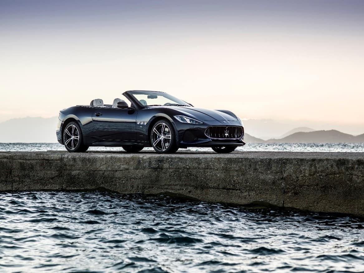 Black Maserati GranTurismo Convertible parked on a pier by the water