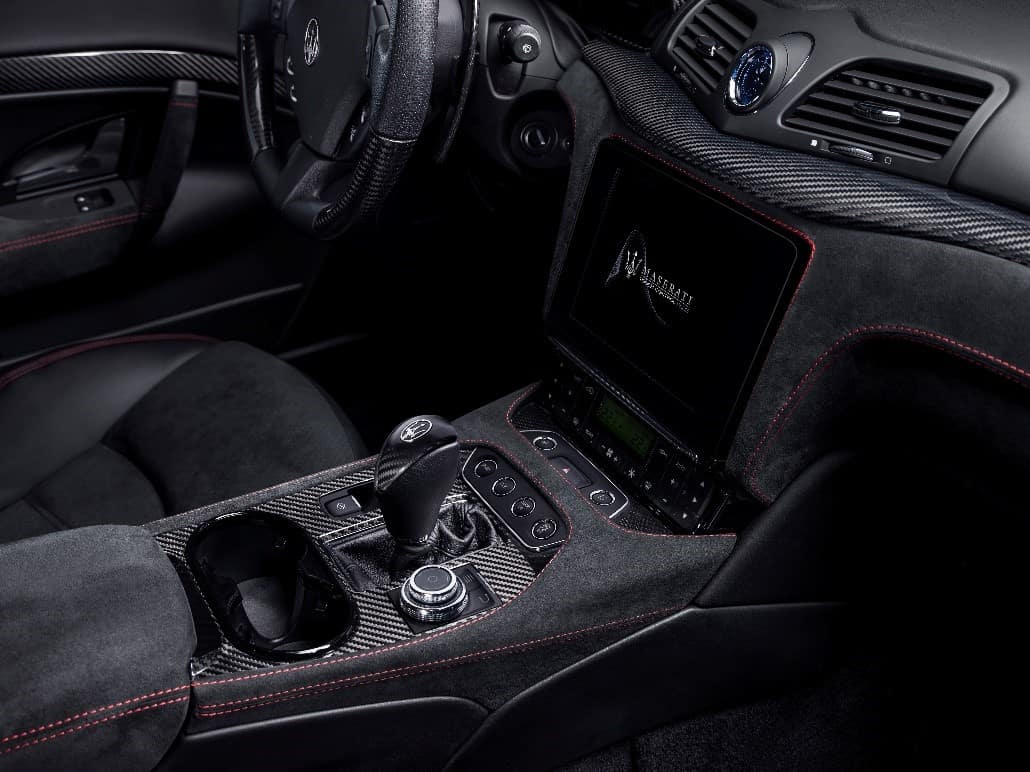 Black interior of a Maserati GranTurismo showcasing the touchscreen and center console rotary control