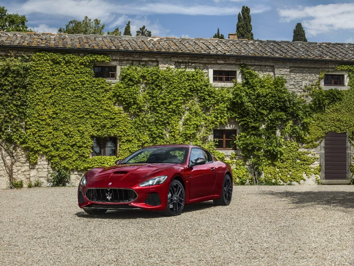 Red Maserati GranTurismo MC parked in front of stone building that is covered in ivy
