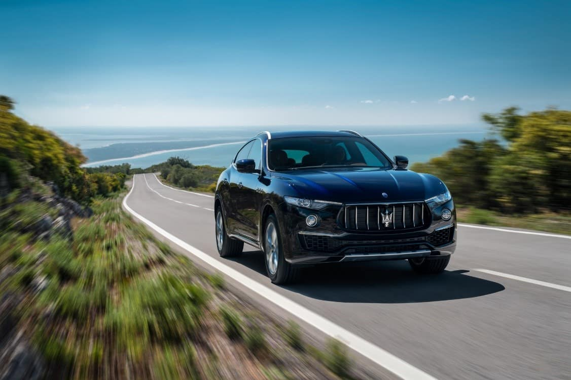 Black 2019 Maserati Levante GranLusso driving on a road with a body of water in the distance