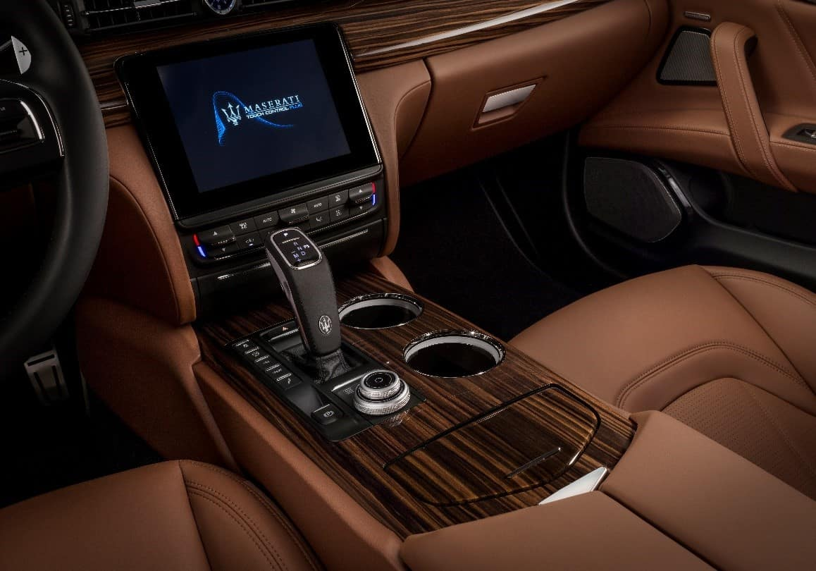 Interior of a 2019 Maserati Quattroporte GranLusso with brown leather and infotainment touchscreen and center console rotary control