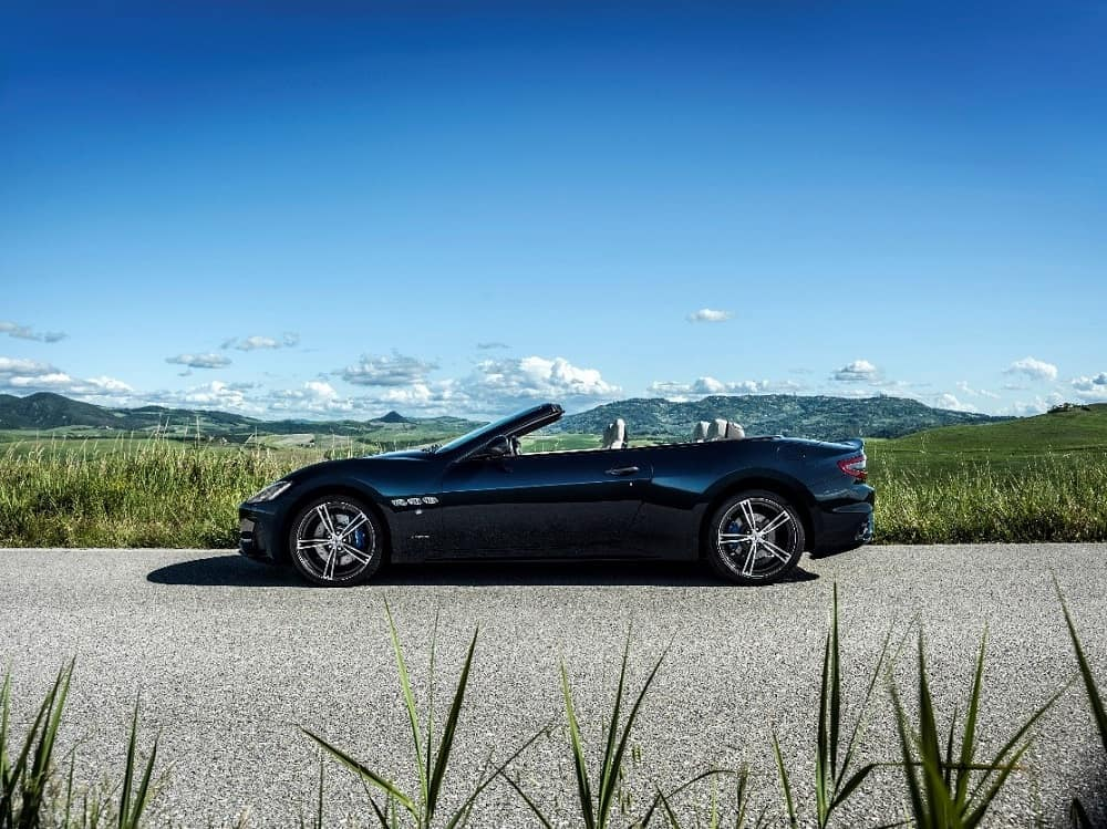 Black 2019 Maserati GranTurismo Convertible car with the top down parked by a grassy field with a blue sky