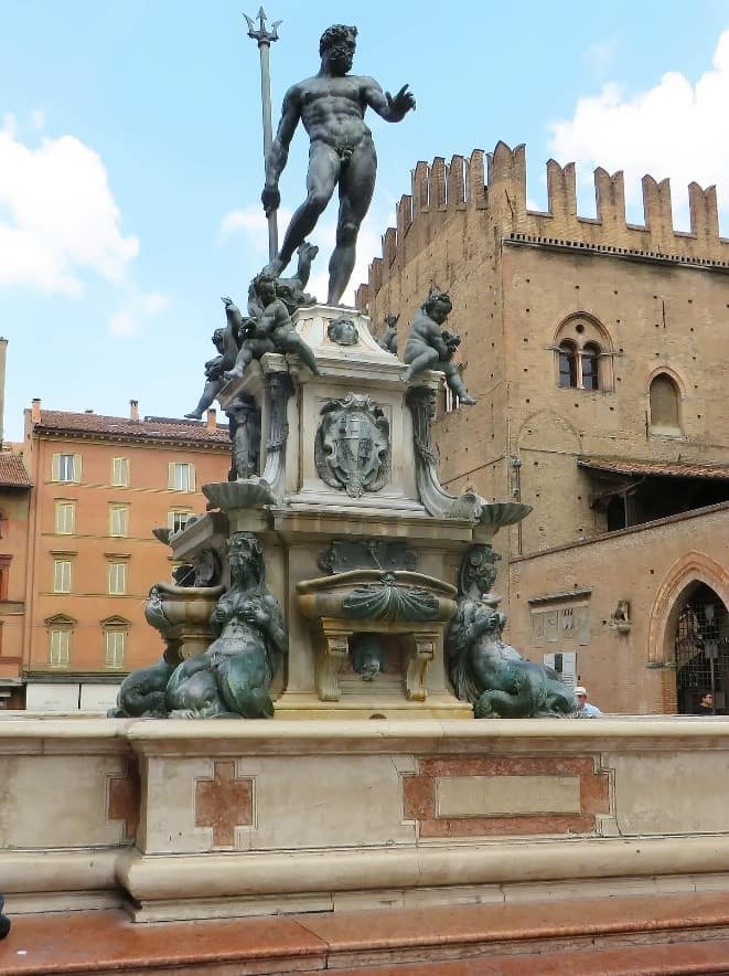 The Neptune statue in Piazza Maggiore in Bologna, Italy surrounded by stone buildings on a sunny day with clouds in a blue sky