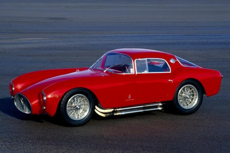 red 1954 Maserati A6GCS Berlinetta Pinin Farina with chrome accents parked on pavement