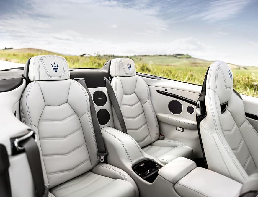 closeup of handcrafted white leather seats in a 2018 Maserati Gran Turismo convertible sport parked next to a grassy field