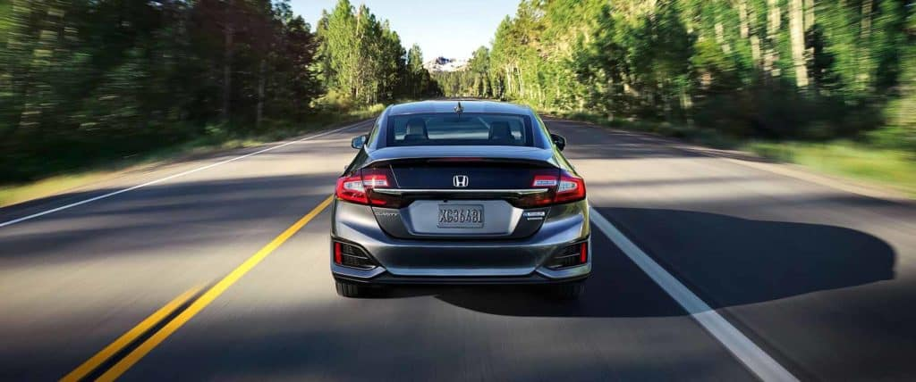 2018 Honda Clarity Plug In Hybrid driving down a road lined with trees