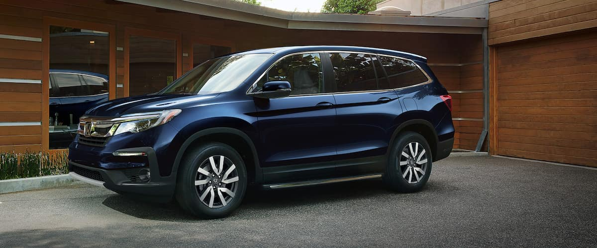 Blue 2021 Honda Pilot parked outside brown one-story home