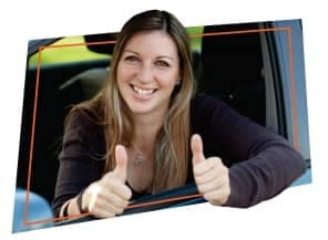 woman leaning out window of car holding her thumbs up