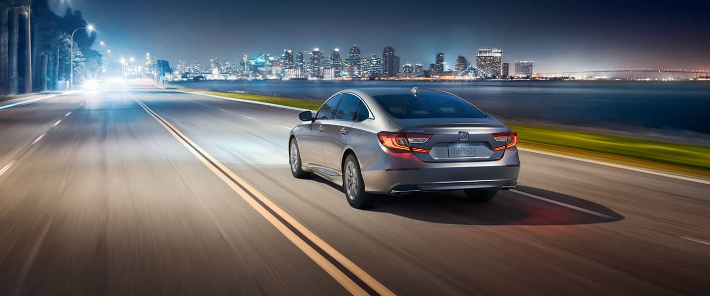 2018 Honda Accord driving on a highway towards the nighttime city lights