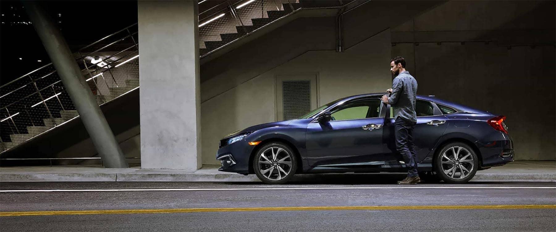 Man entering 2019 Honda Civic Sedan Parked on Side of Road