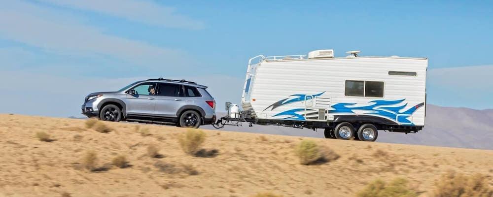 Silver 2019 Honda Passport towing white trailer on desert hill