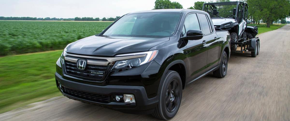 Black 2020 Honda Ridgeline pulling small vehicle on trailer by field