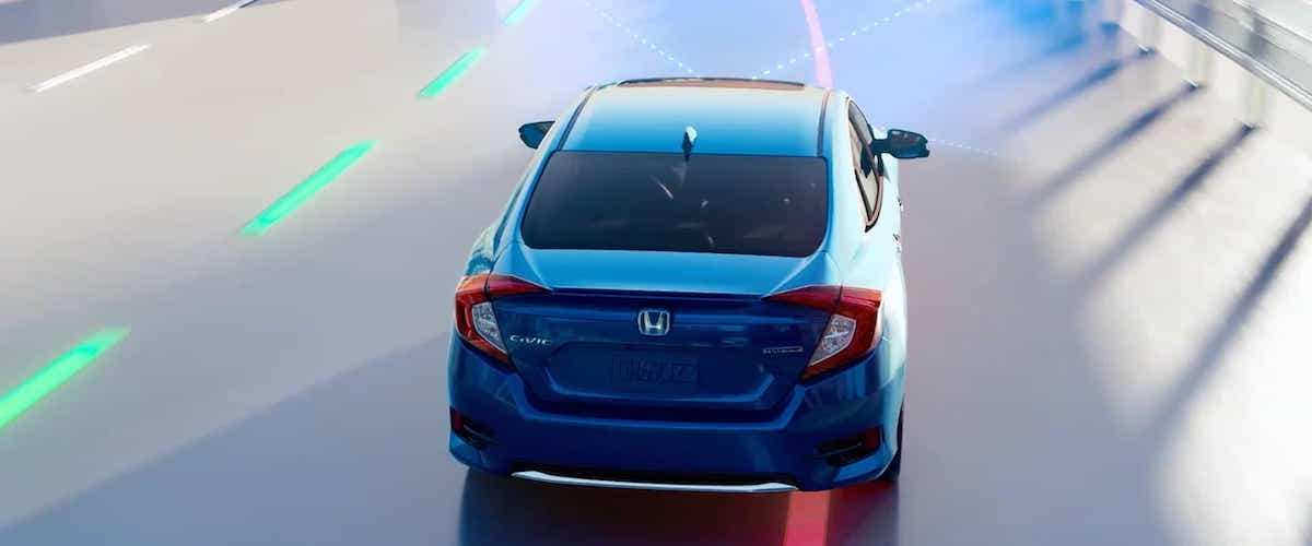 Blue 2020 Honda Civic Sedan with road departure mitigation system concept graphic