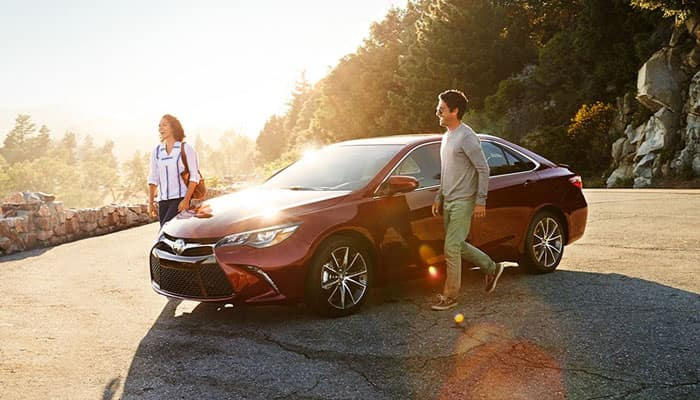 Couple Walking Beside a 2016 Toyota Camry
