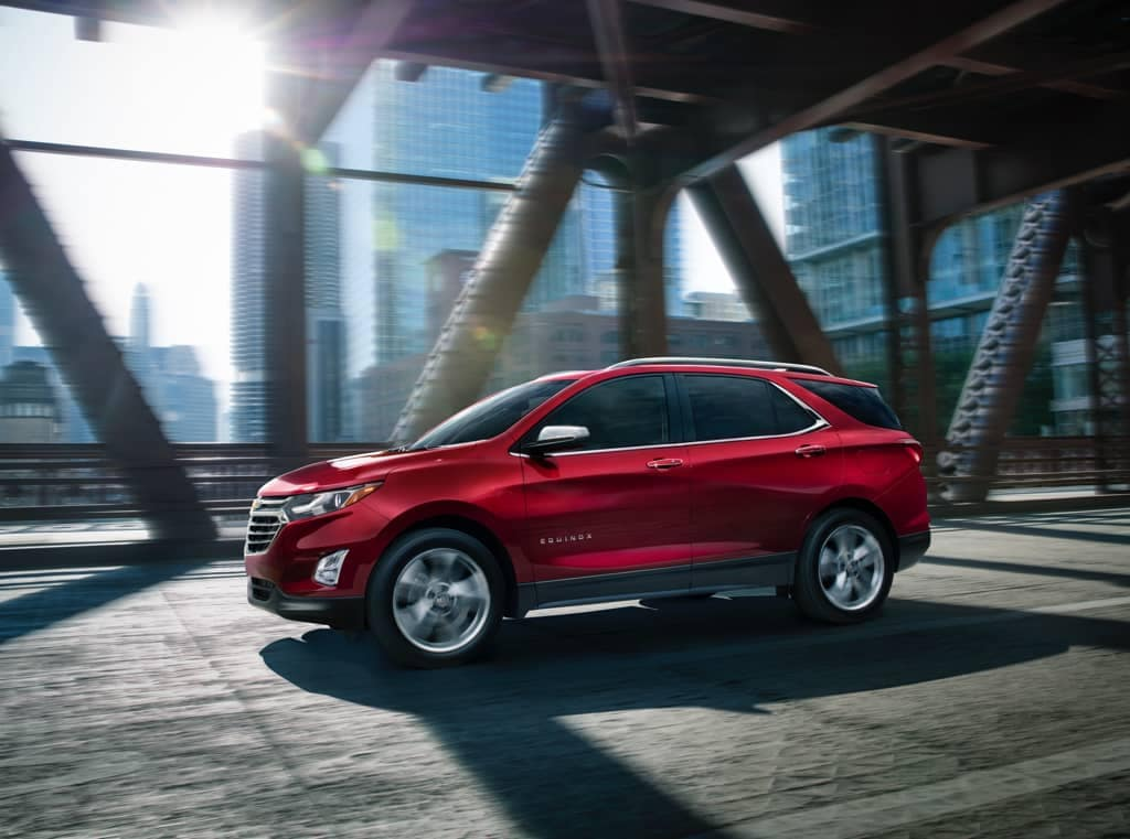 Red Chevy Equinox on city bridge