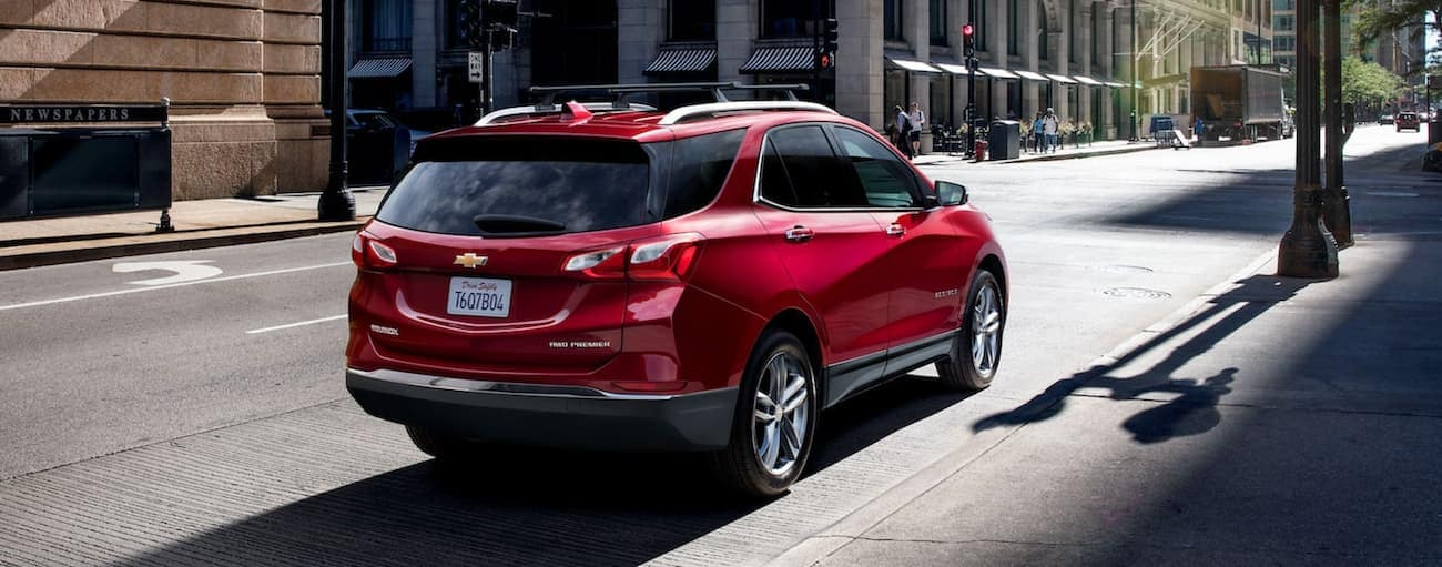 A red 2021 Chevy Equinox is parked on a city street.