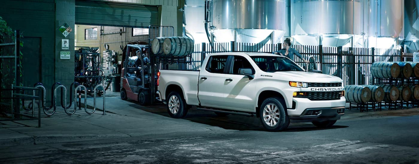 A white 2021 Chevy Silverado 1500 is shown from the side at a loading dock next to a forklift.