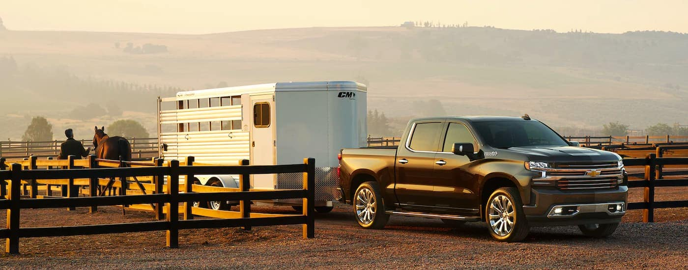A black 2021 Chevy Silverado 1500 is shown from the side attached to a silver horse trailer.