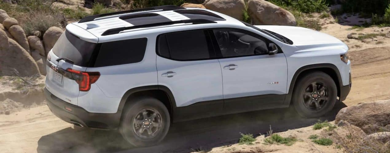 A white 2021 GMC Acadia AT4 is off-roading on a dirt trail.