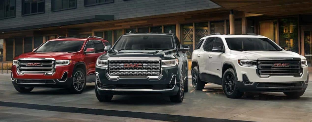 A red, a black, and a white 2021 GMC Acadia are parked in front of a modern building at dusk.