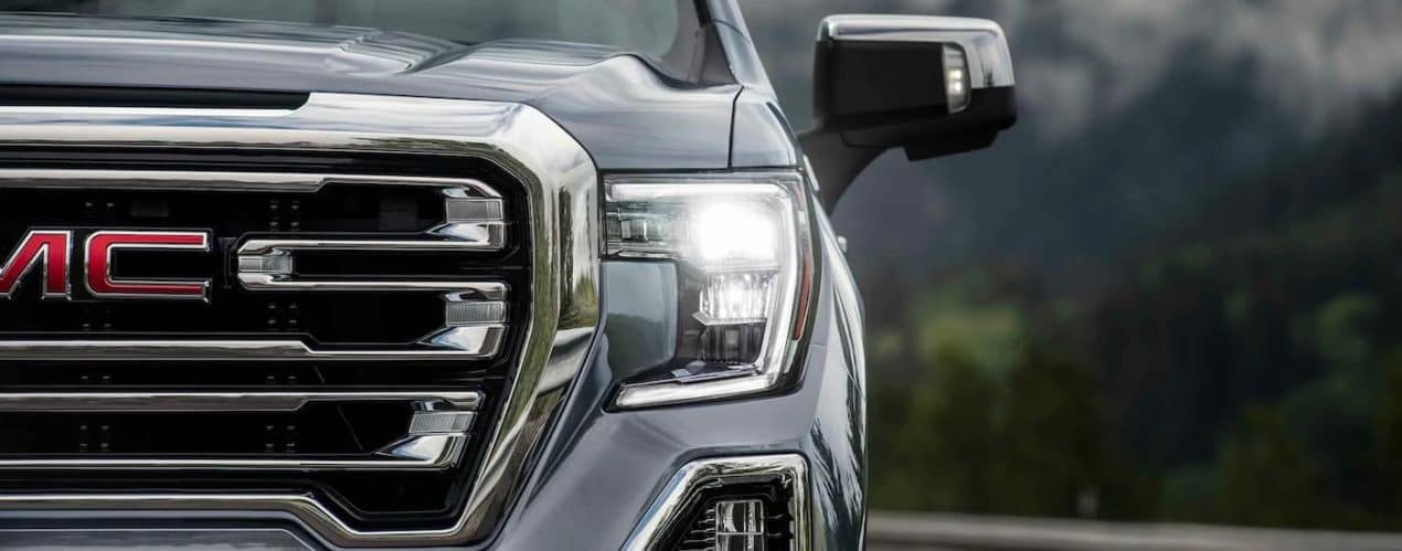 A gray 2021 GMC Sierra 1500 is shown from the front with a close up on the grille and headlight.