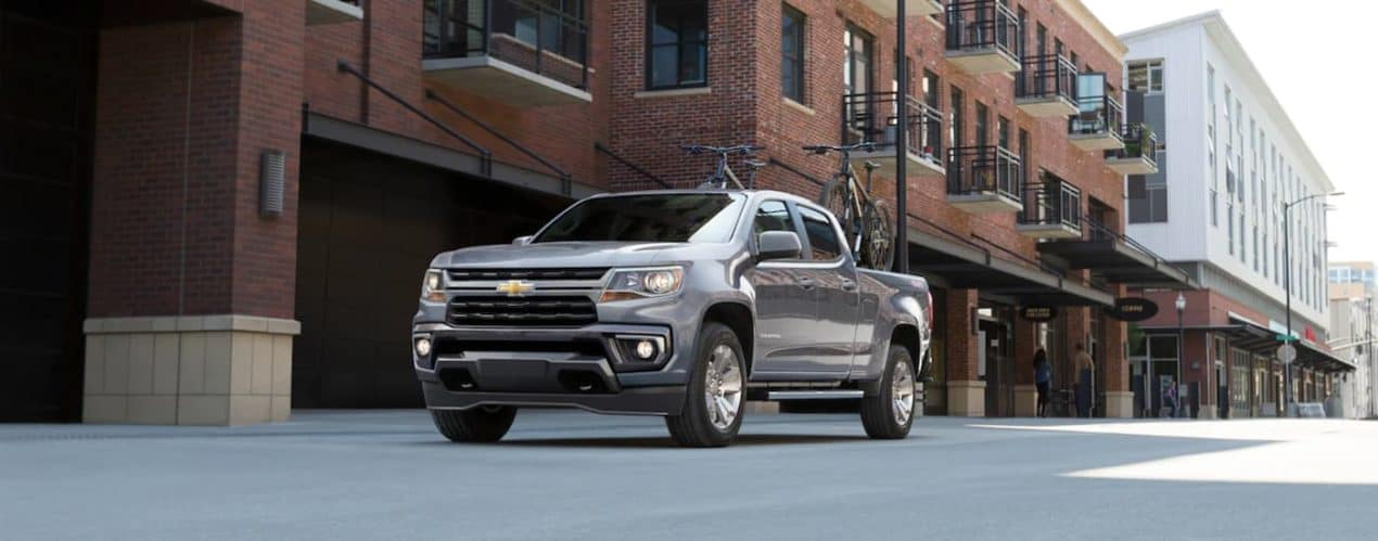 A gray 2021 Chevy Colorado is shown from the front, parked in front of a brick building.