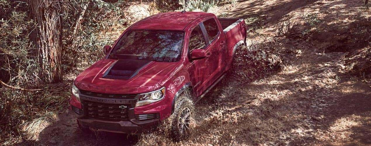 A red and black 2021 Chevy Colorado ZR2 is shown from a high angle, off-roading in the woods.