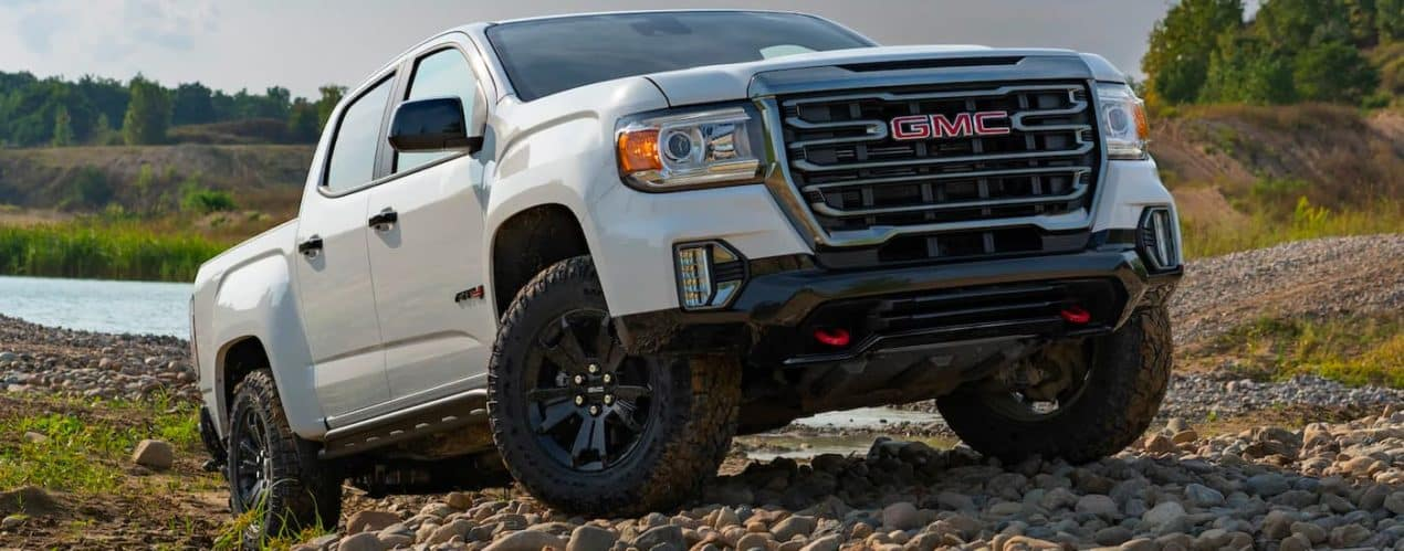 A white 2021 GMC Canyon Elevation AT4 is shown parked on a rocks with a lake in the background.
