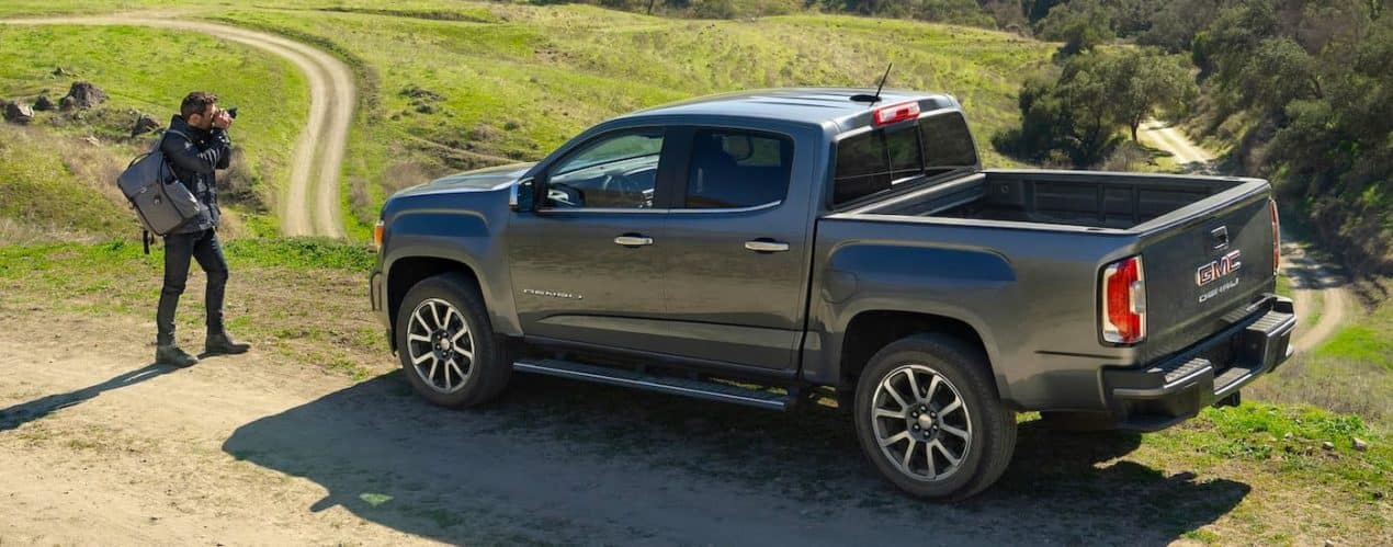 A gray 2021 GMC Canyon Denali is shown from a high angle parked next to a photographer.