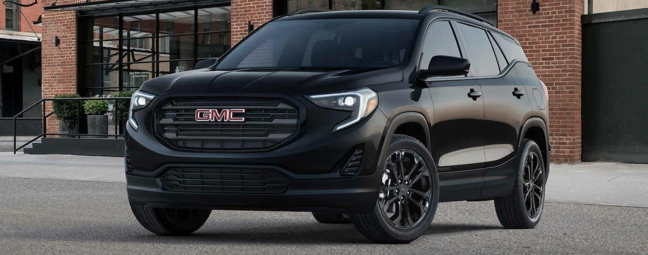 A black 2021 GMC Terrain is parked in front of a brick building.