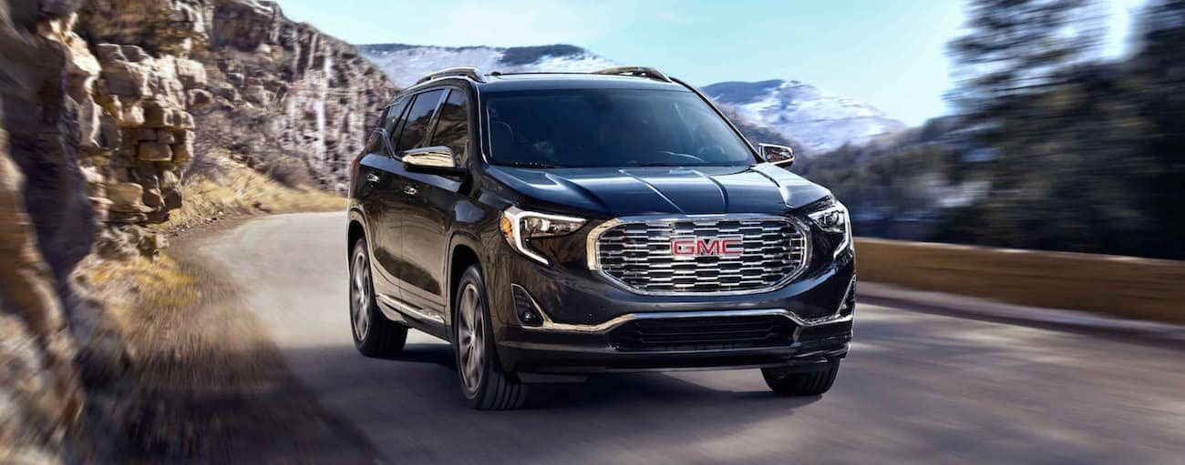 A black 2021 GMC Terrain is driving on a mountain road.
