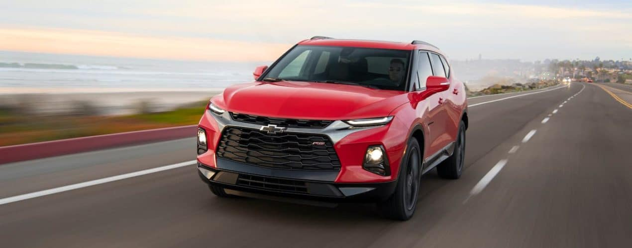A red 2021 Chevy Blazer RS is driving down and empty highway.
