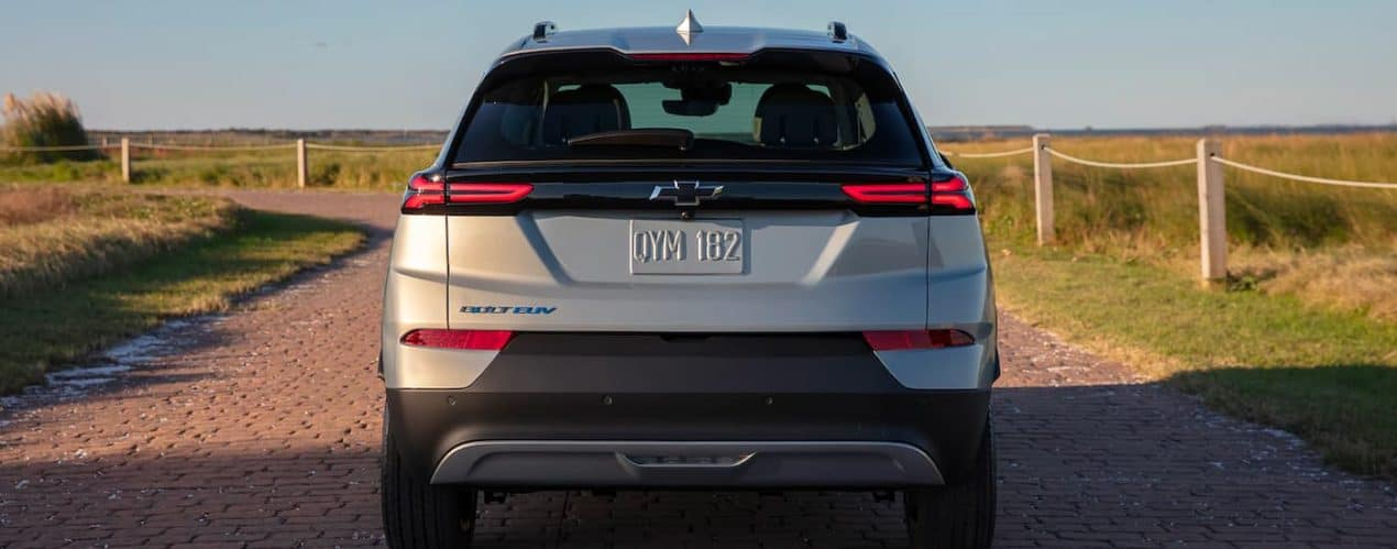 A silver 2022 Chevy Bolt EUV is shown from the rear driving down a paver pathway.