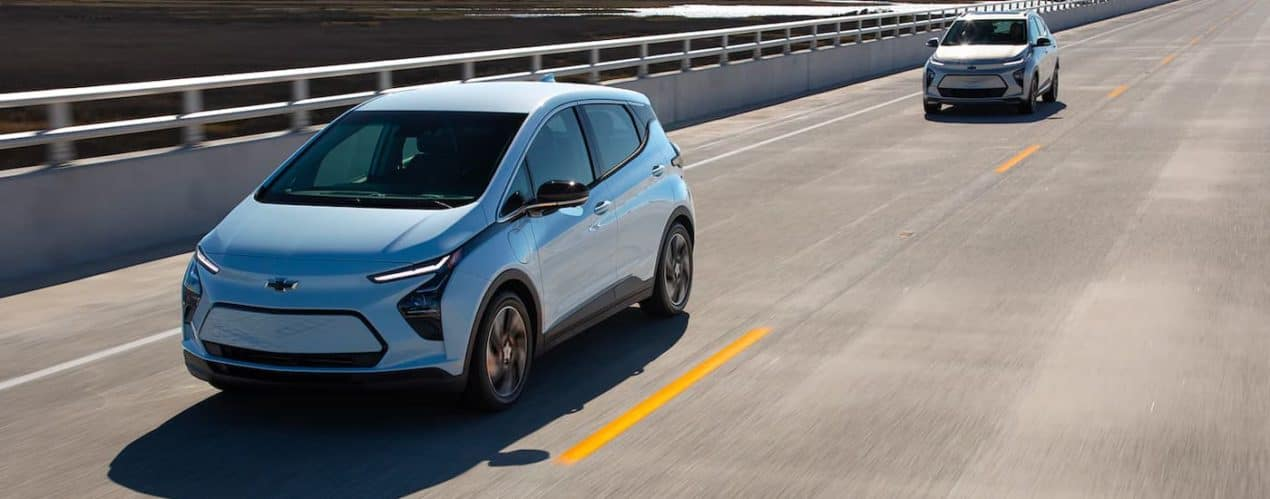 A light blue 2022 Chevy Bolt EV is shown driving down a highway followed by a 2022 Chevy Bolt EUV.