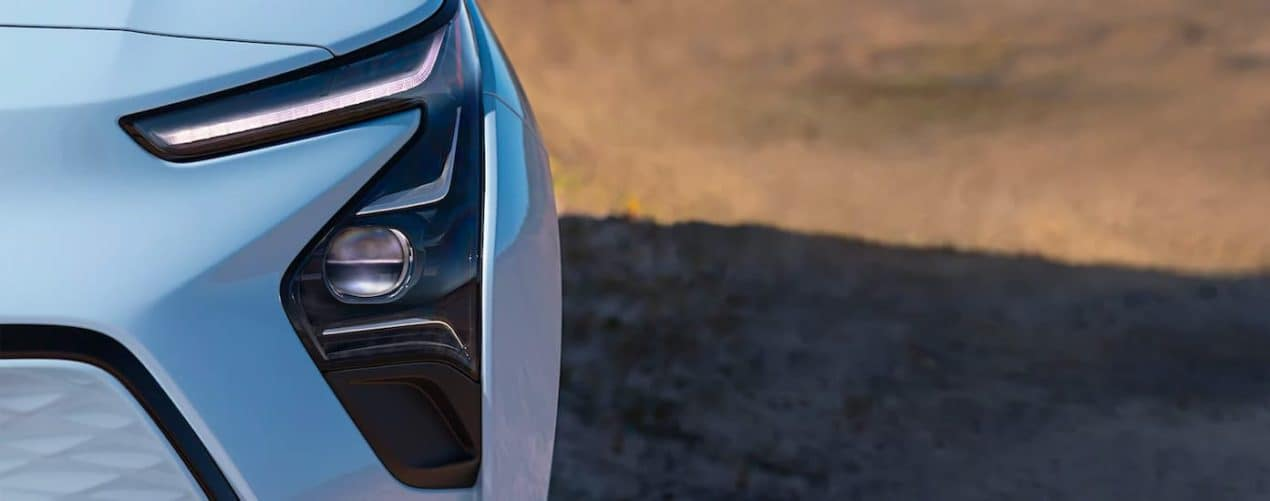 A close up shows the head light and fog light on a light blue 2022 Chevy Bolt EV.