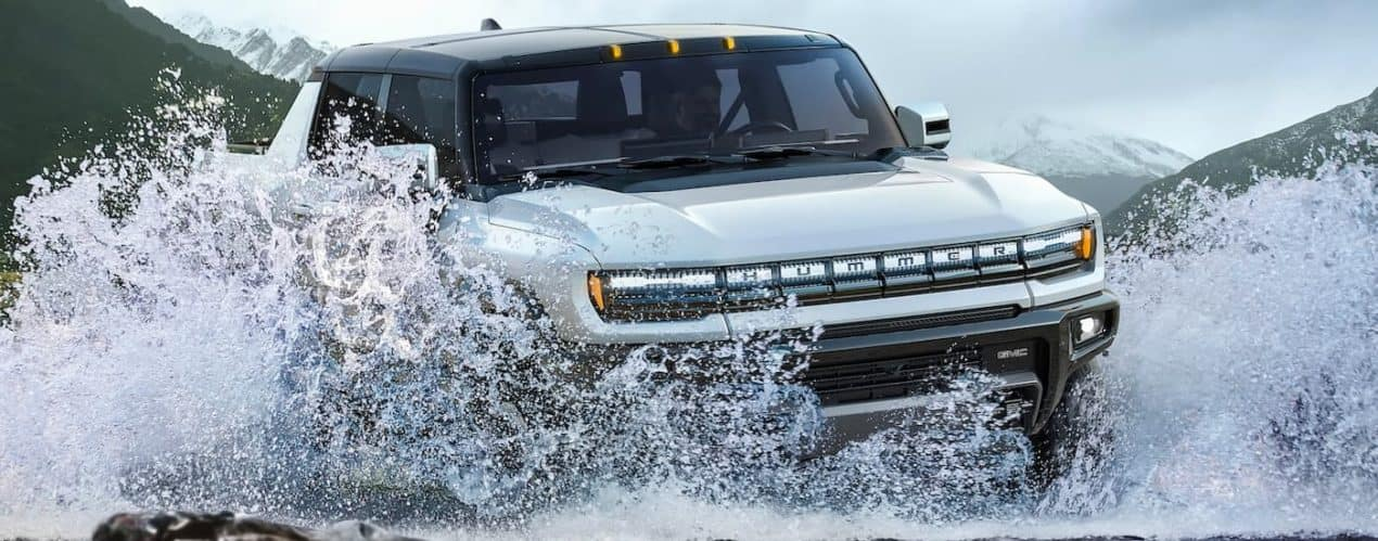 A white 2022 GMC Hummer EV truck is shown from the front splashing through a river.