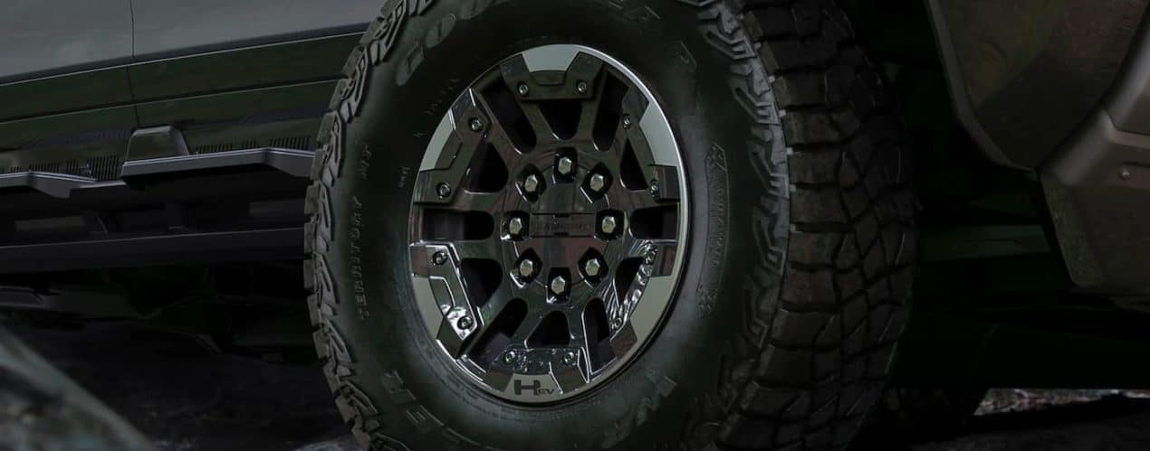 A close up shows the passenger side front wheel on a gray 2022 GMC Hummer EV truck.