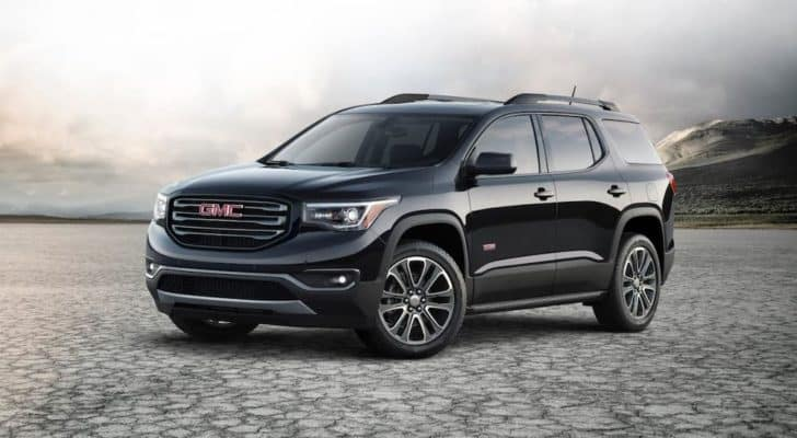 A black 2021 Acadia is parked in a flat desert.