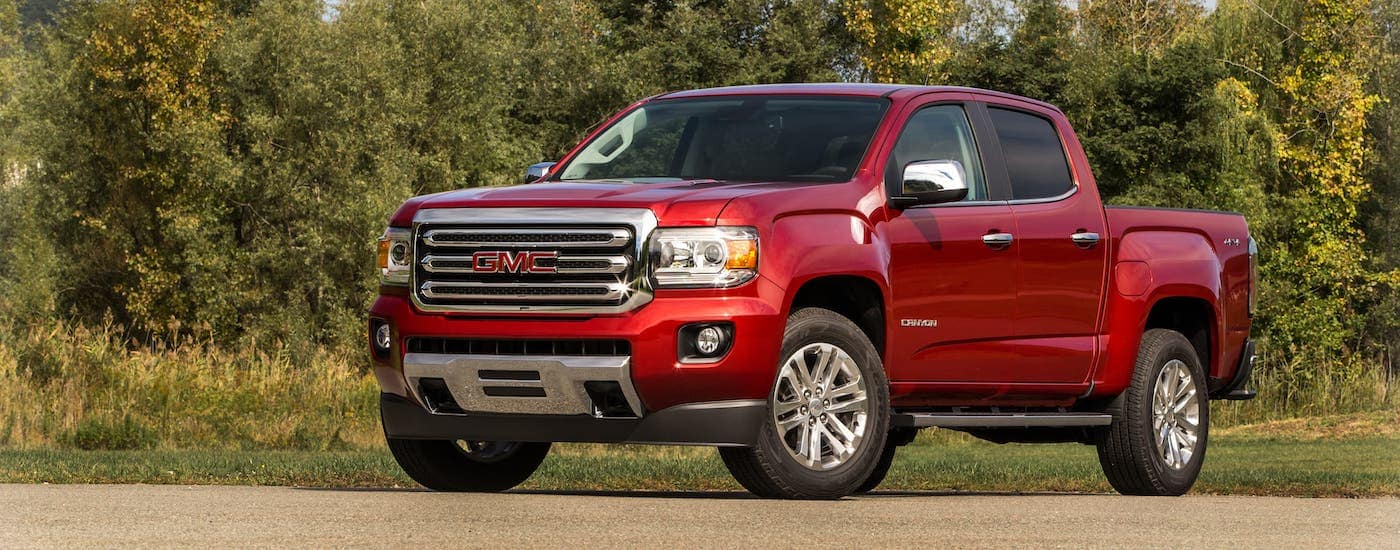 A red 2021 GMC Canyon is parked in front of trees after leaving a GMC Dealer Near you.