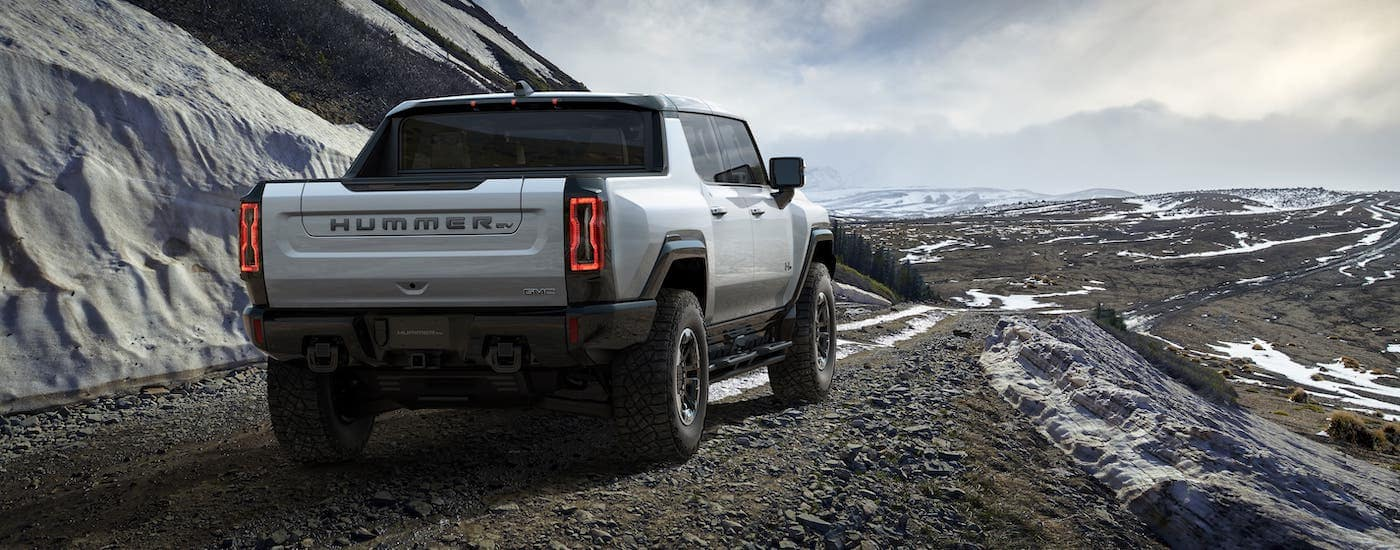 A silver 2022 GMC Hummer EV is shown from the rear while driving on a snowy mountain trail.