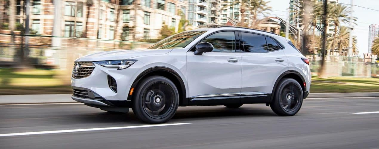 A white 2021 Buick Envision is shown from the side speeding down a city street.
