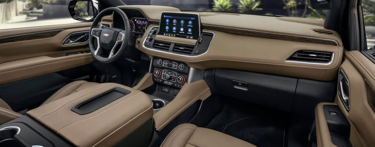 The tan front interior and infotainment screen is shown in a 2021 Chevy Suburban.
