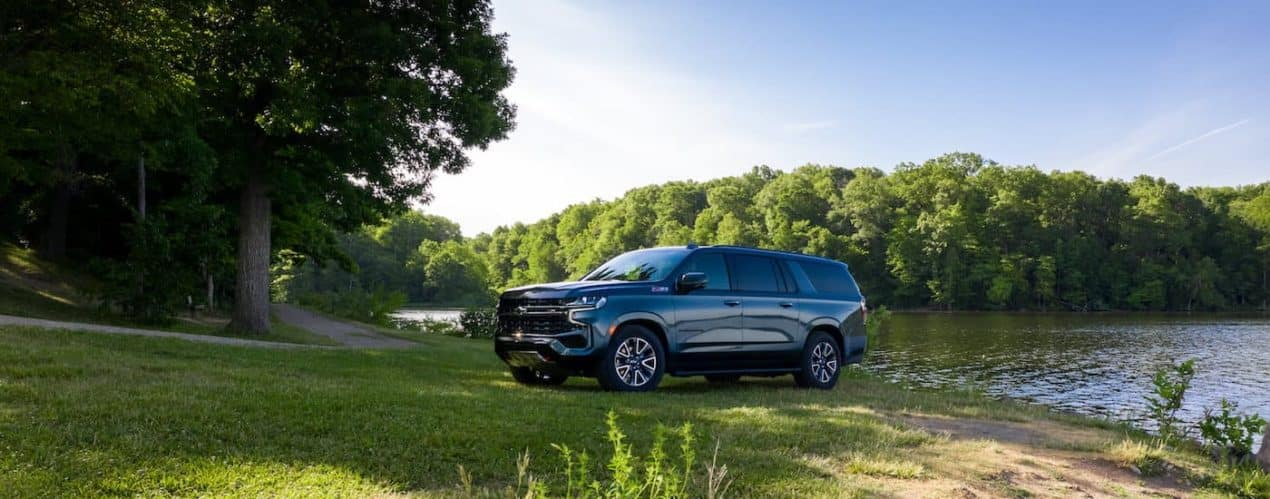 A grey 2021 Chevy Suburban Z71 is shown parked in the shade next to a lake.