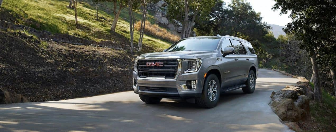 A gray 2021 GMC Yukon is shown driving down a country road.