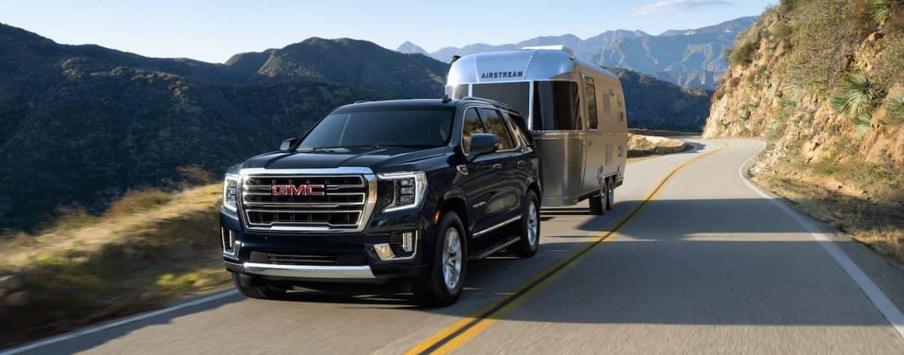 A black 2021 GMC Yukon is shown towing an Airstream trailer down a mountain road.