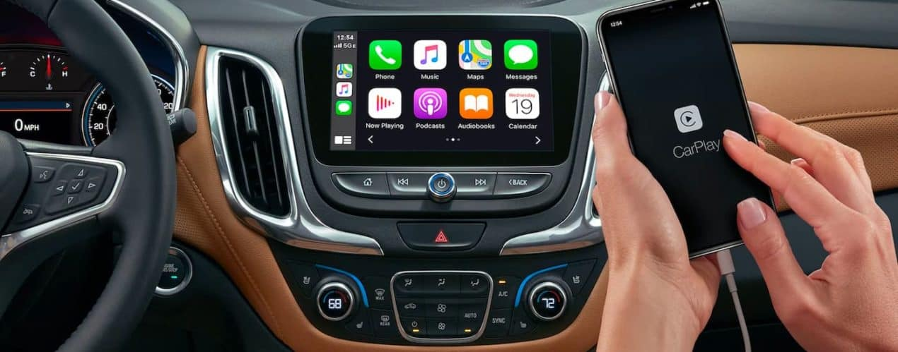 A close up shows the infotainment screen and smart phone being used in a 2021 Chevy Equinox.