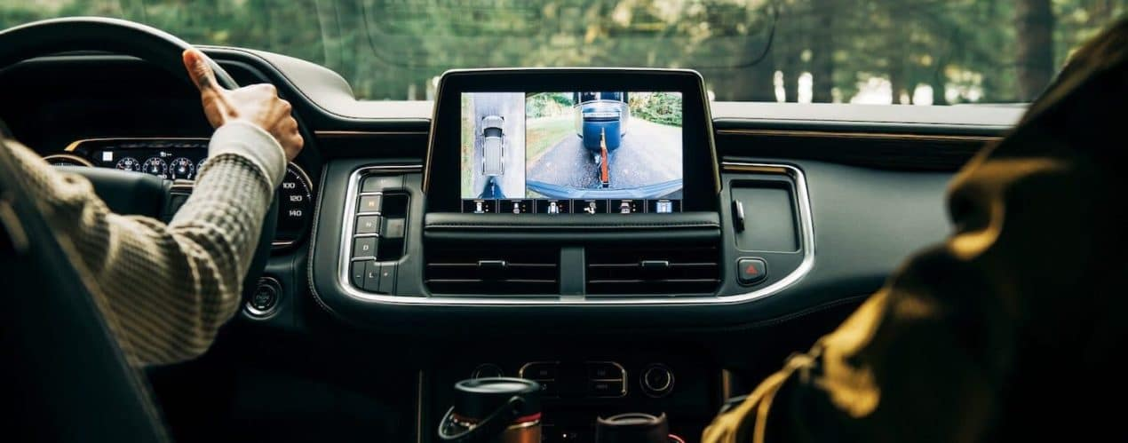 The interior is shown in a 2021 Chevy Tahoe High Country with a trailer on the infotainment screen.